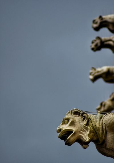 Low angle view of gargoyles against clear sky