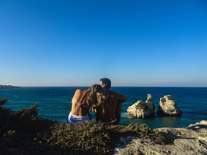 Friends sitting on rocks by sea against clear blue sky