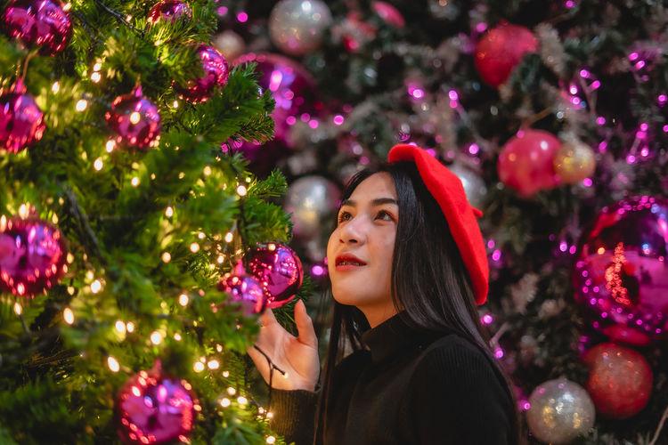 Close-up of beautiful young woman touching illuminated christmas tree