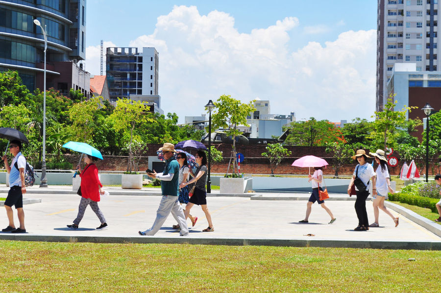 Tourists crossing square near museum in Da Nang, Vietnam. Architecture Casual Clothing City City Street Cloud Da Nang Day Grass Helicopters Lawn Leisure Activity Medium Group Of People Mixed Age Range Modern Museums Outdoors Sky Tourism Tourists Tree Umbrellas Vietnam Walking