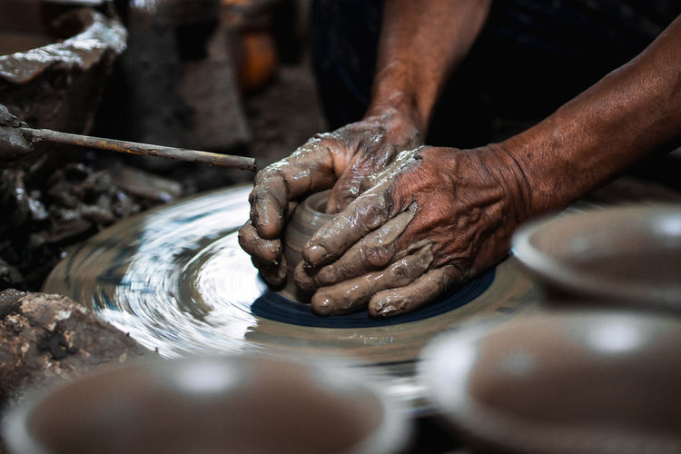 Cropped hands of man making pottery in workshop