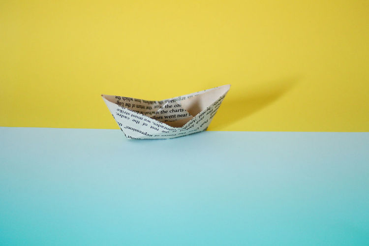 High angle view of paper boat on colored background