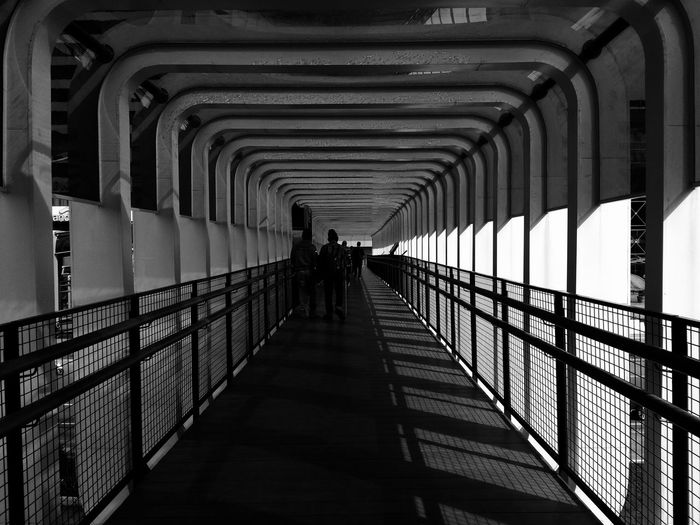 Men Prison Full Length Silhouette Railing Walking Architecture Built Structure Archway Arch Bridge vanishing point Diminishing Perspective The Way Forward Footbridge Bridge - Man Made Structure Passageway Arch Pathway