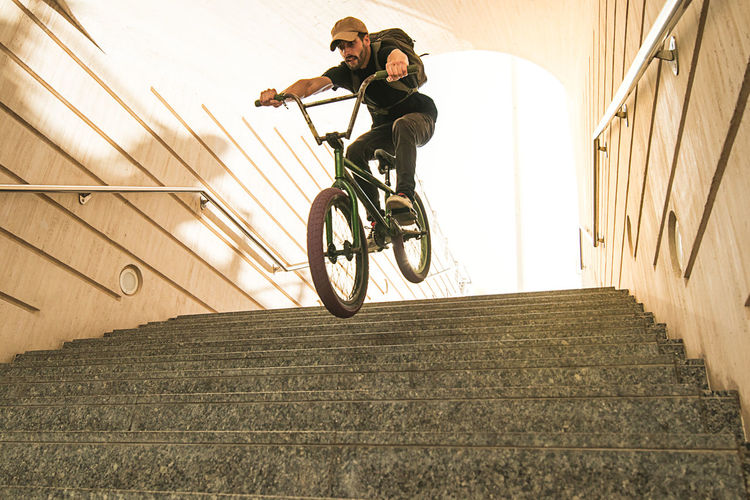 Man riding bicycle on staircase against wall