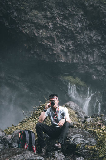 Young man sitting on rock against waterfall