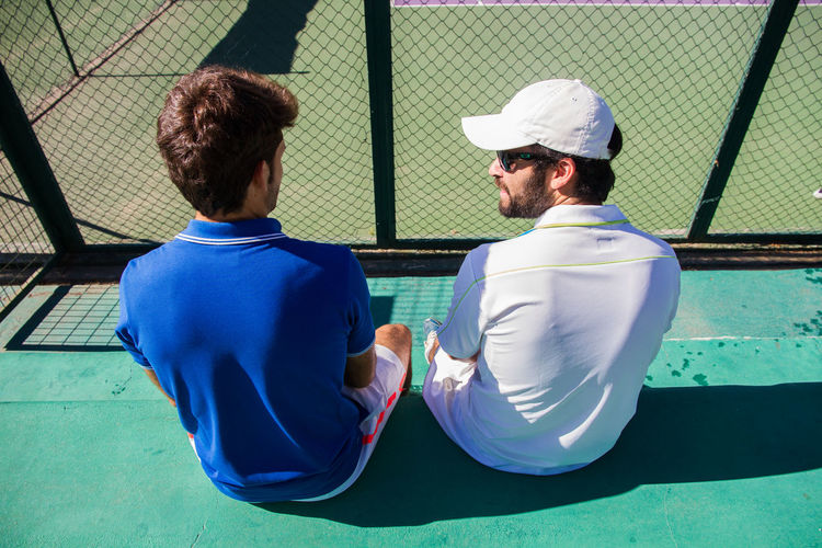 Two professional tennis players talking while resting sitting on a sunny day. Court Exercising Field Lifestyle Set Sitting Tennis Activity Athletes Ball Caucasian Competition Game Leisure Activity Match - Sport Men Pause Professionals Racket Sport Resting Sport Sportwear Talking Two People Young Adult