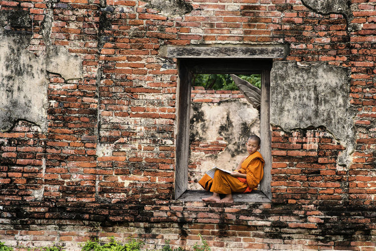 Monk reading book while sitting on entrance of old building