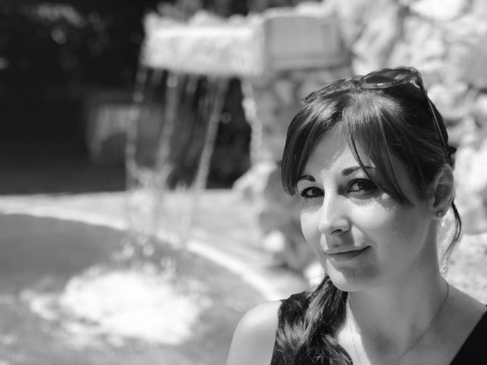 Portrait of smiling beautiful woman with fountain in background