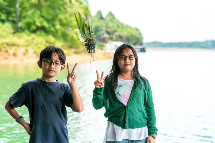 Siblings, boy and girl wearing glasses showing peace sign while travelling to the lake.