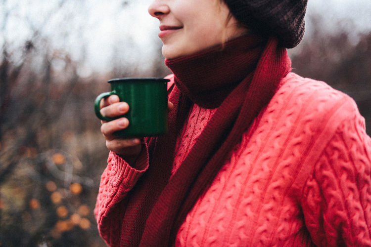 Midsection of woman holding coffee cup outdoors