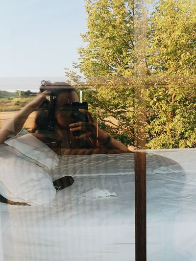 Reflection of man photographing on glass window