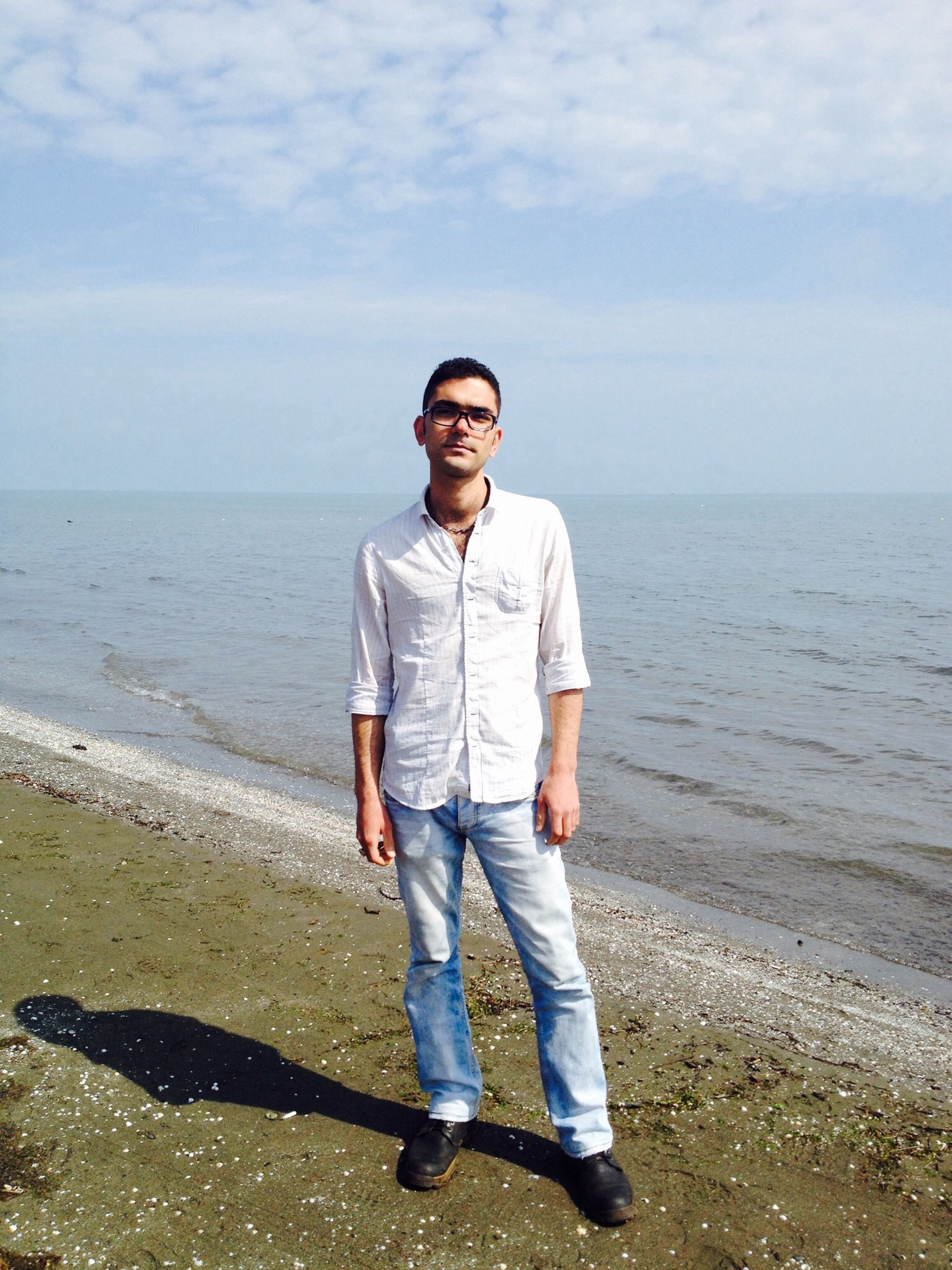 water, sea, casual clothing, sky, beach, horizon over water, full length, person, lifestyles, shore, standing, leisure activity, front view, childhood, looking at camera, elementary age, nature, three quarter length