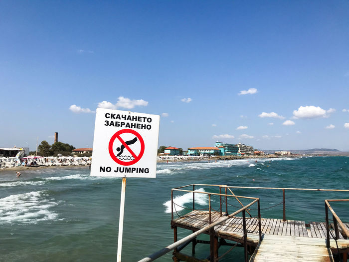Warning sign by sea against sky