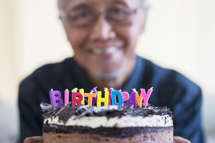 Portrait of senior man holding birthday cake in home
