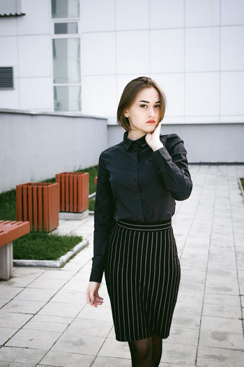 street portrait of a student girl dressed fashionably in dark clothes, on an autumn sunny day Architecture Beautiful Woman Building Exterior Built Structure Day Fashion Leisure Activity Lifestyles One Person Outdoors Real People Standing Warm Clothing Young Adult Young Women