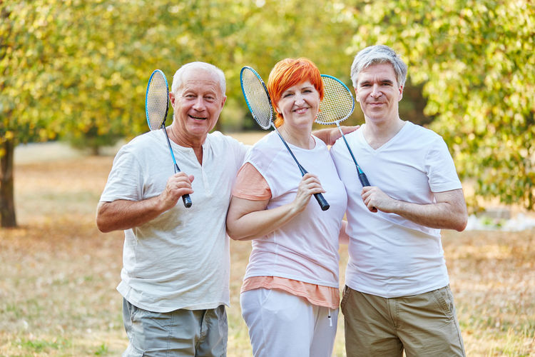 Smiling Senior Men And Woman Playing Badminton While Standing On Grassland Against Trees