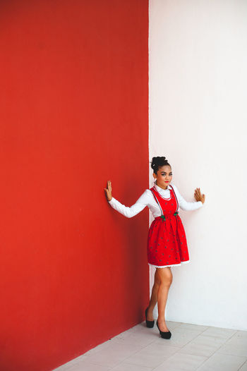 Full length of smiling girl standing against red wall