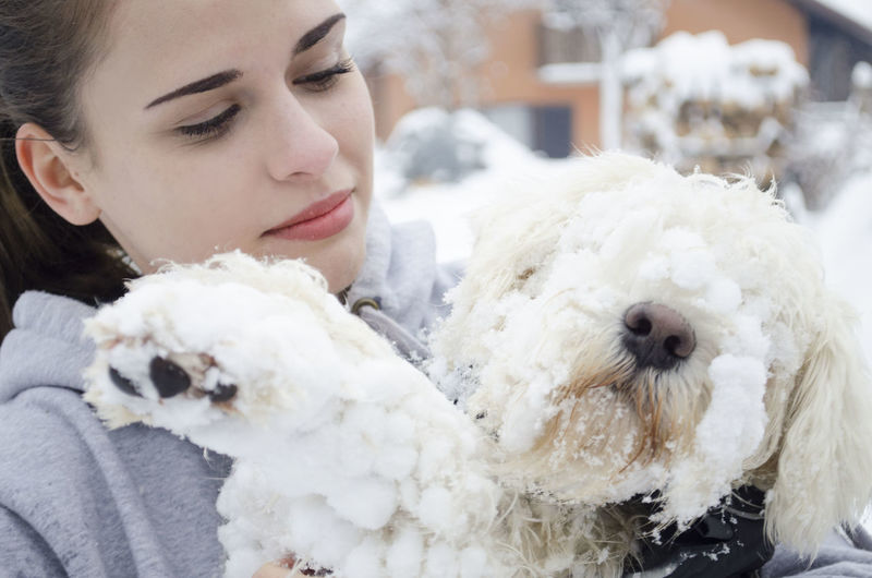 Portrait of young woman with dog on snow