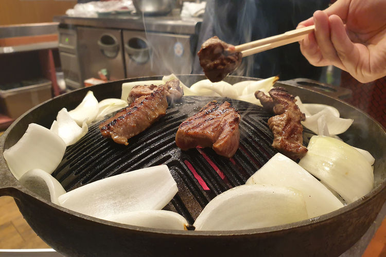 Close-up of person preparing food on barbecue grill
