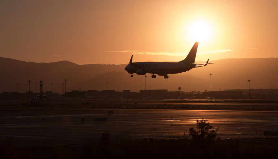Silhouette airplane flying over runway against sky during sunset
