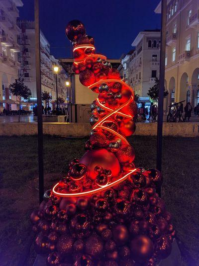 Illuminated christmas tree on street against building at night