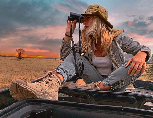 Woman looking through binoculars while sitting on car roof against sky during sunset