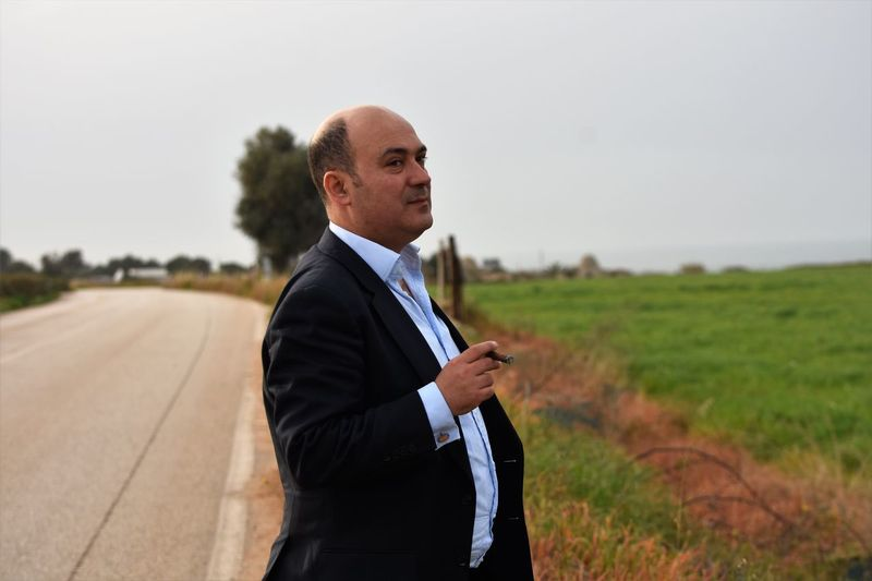 Side View Of Businessman Smoking Cigar While Standing At Roadside