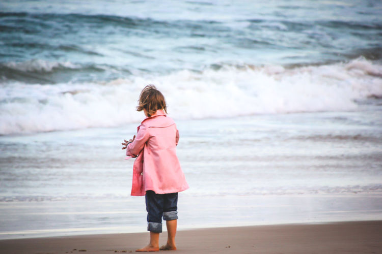 Girl standing on shore at beach