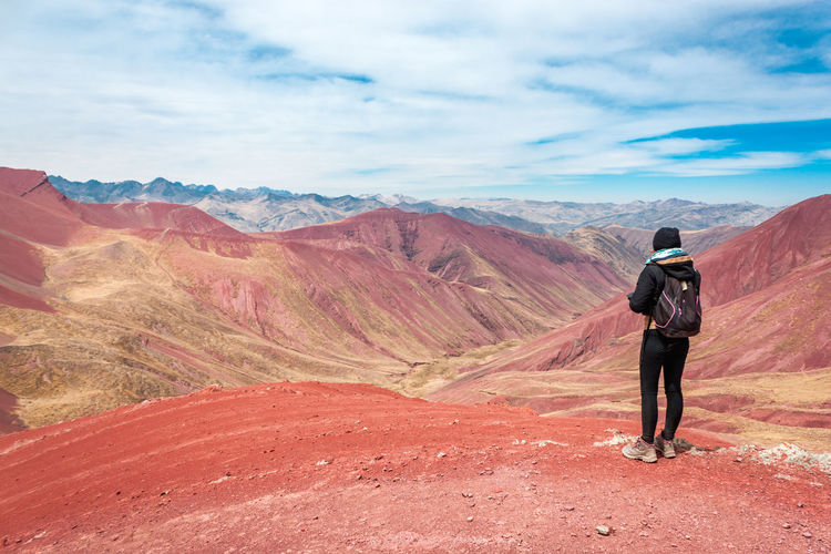 Girl enjoys the view of the reddish mountains , pitumarca - Peru Red Trekking Woman Adventure Beauty In Nature Environment Full Length Hiking Landscape Leisure Activity Lifestyles Looking At View Mountain Mountain Range Nature Non-urban Scene One Person Outdoors Real People Rear View Scenics - Nature Sky Standing Tranquility Travel