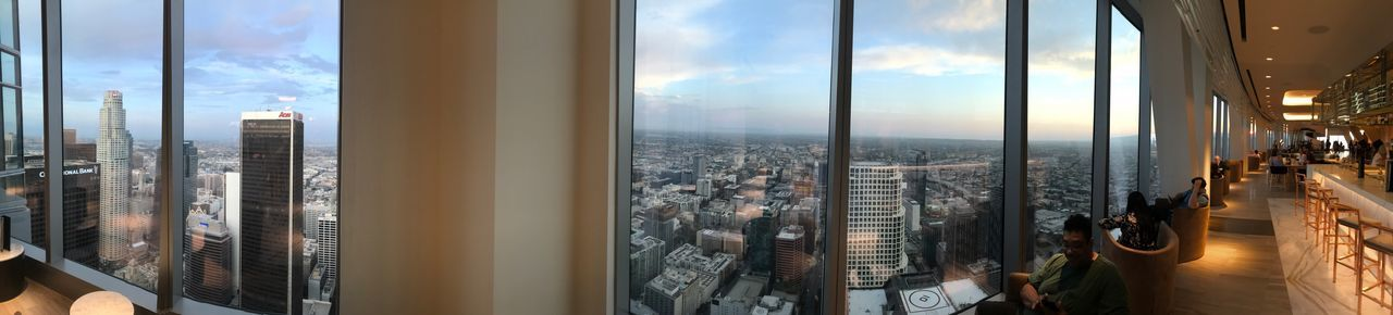 Panoramic view of cityscape against sky seen through window