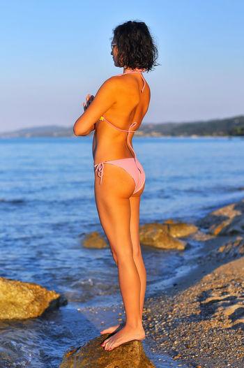 Woman In Bikini Practicing Yoga At Sea Shore