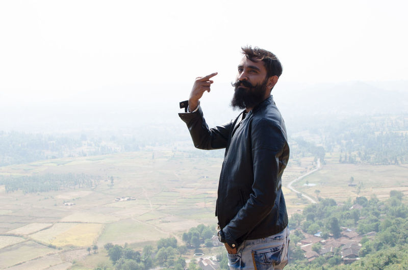 Portrait of bearded young man showing obscene gesture at mountain