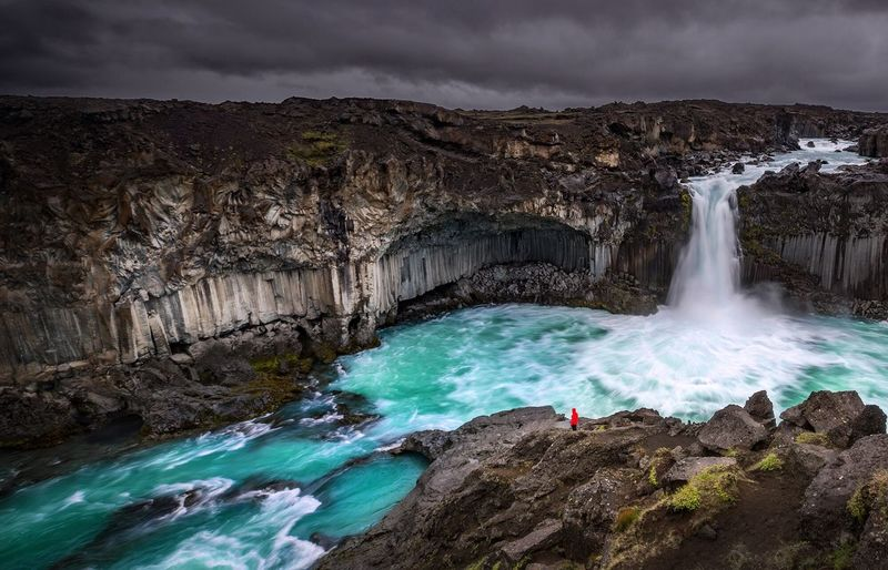 Scenic View Of Waterfall Against Stormy Clouds
