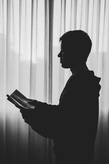 Silhouette man looking at book at home