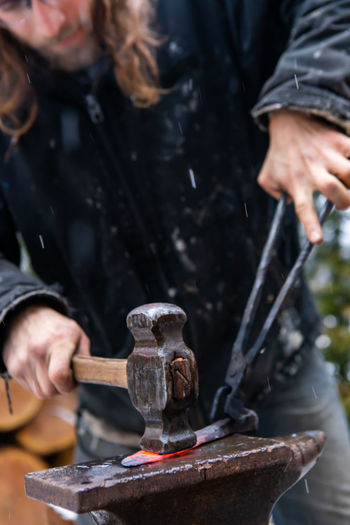 Midsection of blacksmith working in workshop