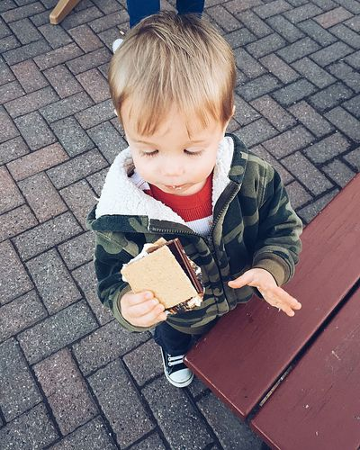 High Angle View Of Boy Holding Smore At Street