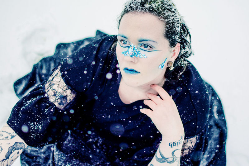 Portrait of beautiful woman standing against snow