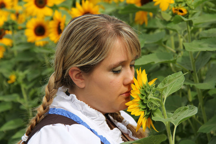 Close-Up Of Woman With Braided Hair Smelling Sunflower