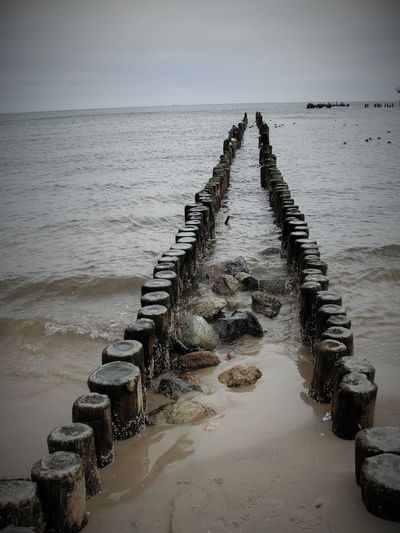 Wooden posts leading into the sea