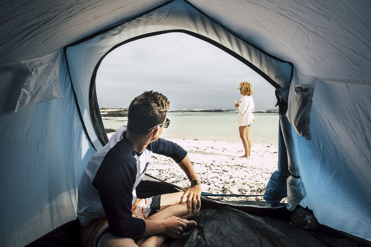 Alternative vacation enjoying total freedom with tent camped on the white sandy beach and blue ocean and sky. couple of caucasian people enjoying the world in wanderlust. summer holiday and enjoy the nature traveling Camping Mother Adult Casual Clothing Couple - Relationship Curly Hair Day Leisure Activity Lifestyles Men Mode Of Transportation Nature Outdoors People Real People Sitting Sky Teenager Tent Togetherness Transportation Two People Water Women Young Adult