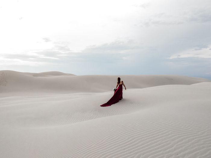 Woman on sand dune in desert against sky