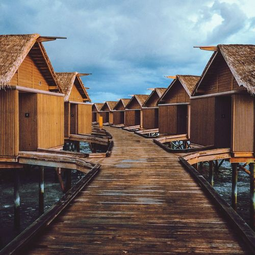 Stilt houses in row over river against cloudy sky