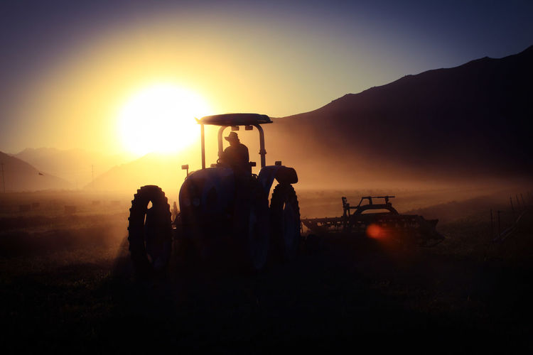 Silhouette people on tractor against mountain ragainst sky during sunrise
