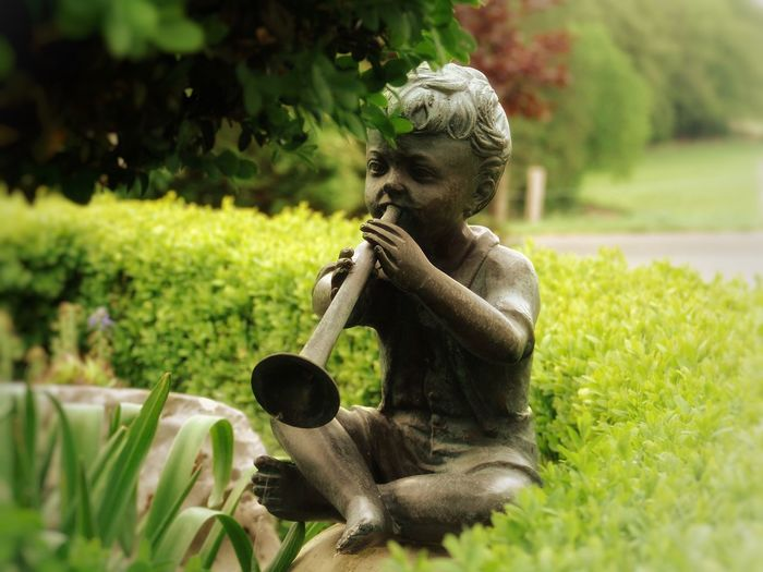 Statue of boy playing musical instrument