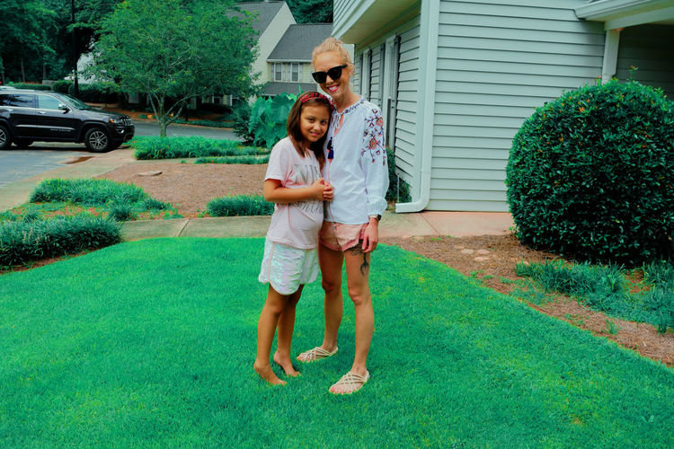 Full length of woman and girl standing at lawn