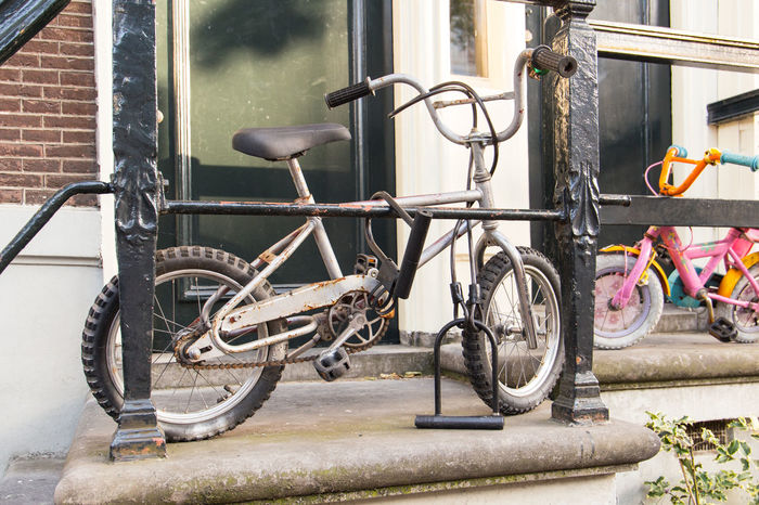 Amsterdam Kids Bike Locked Netherlands Railing Abandoned Architecture Bicycle Building Exterior Built Structure Day Holland Outdoors Stationary Tourist Destination Wheel Window