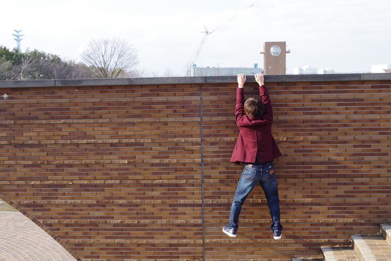 Full length of girl standing against brick wall