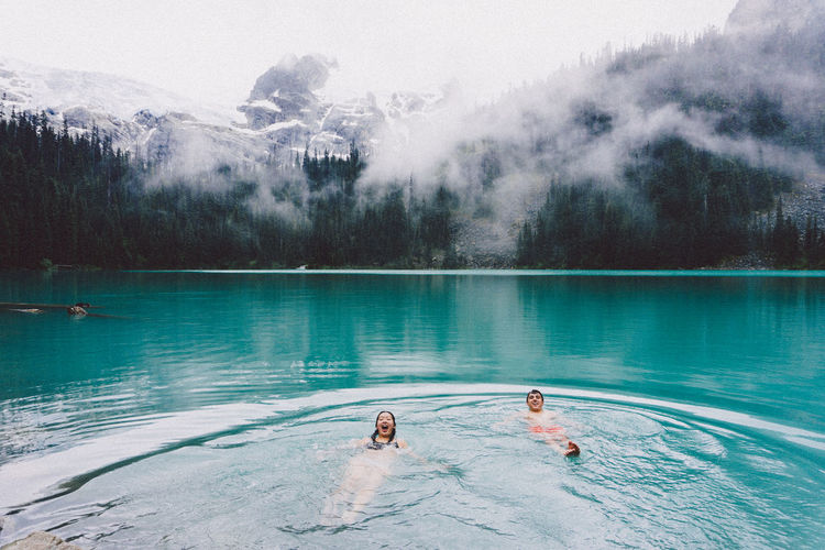 Friends swimming in lake during foggy weather