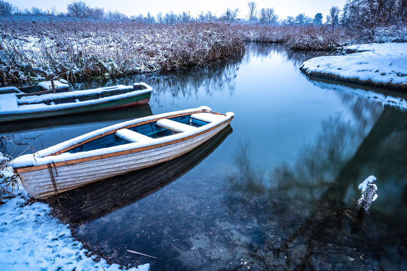 Copy Space Reflection Rowboat Tranquil Scene Moored Ice Frozen Frost Waterfront Riverside River Outdoors Snow Plant Beauty In Nature Tree Cold Temperature Winter No People Nature Day Tranquility Mode Of Transportation Transportation Water