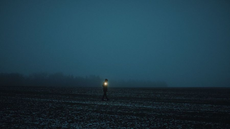 Man with flashlight walking on land against sky at night